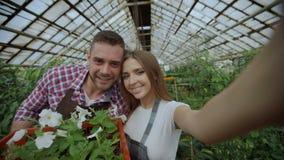 Jardineros cariñosos alegres de los pares que toman la imagen del selfie en cámara del smartphone y que se besan mientras que tra almacen de video