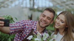 Jardineros cariñosos alegres de los pares que toman la imagen del selfie en cámara del smartphone y que se besan mientras que tra almacen de metraje de vídeo