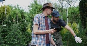 Jardineros que examinan la planta metrajes