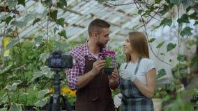 Jardineros sonrientes jovenes de los pares del blogger en el delantal que sostiene la flor que hablan y blog video de registració metrajes