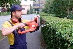 Jardinier à l'aide d'une tondeuse de haie photographie stock libre de droits