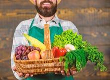 Jardinier barbu d'homme pr?sent ? l?gumes d'eco le fond en bois L?gumes organiques frais dans le panier en osier Fermier photo libre de droits