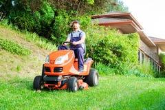 Jardinier conduisant une tondeuse à gazon d'équitation dans le jardin photographie stock libre de droits