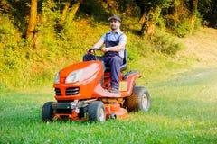 Jardinier conduisant une tondeuse à gazon d'équitation dans le jardin photographie stock