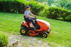 Jardinier conduisant une tondeuse à gazon d'équitation dans le jardin photo libre de droits
