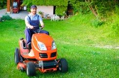 Jardinier conduisant une tondeuse à gazon d'équitation dans le jardin images libres de droits
