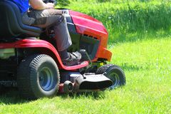 Jardinier conduisant une tondeuse à gazon d'équitation dans un jardin images stock