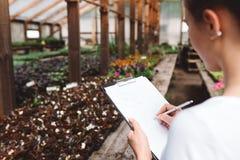 Jardinier de femme professionnelle travaillant en serre chaude photographie stock