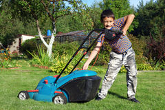 Jardinier de garçon fauchant la pelouse photos stock