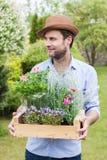 Jardinier de sourire heureux jugeant la boîte en bois pleine des jeunes plantes de fleur dans pots image libre de droits