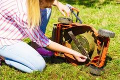 Jardinier féminin avec la tondeuse à gazon cassée Photos stock
