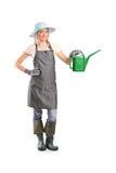 Jardinier féminin de sourire avec le bidon d'arrosage Photographie stock
