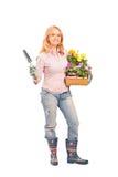 Jardinier féminin retenant les fleurs et le matériel de jardinage image stock