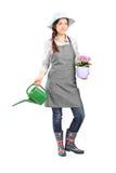 Jardinier féminin tenant une boîte d'arrosage images libres de droits