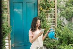 Jardinier f?minin ? l'aide du t?l?phone portable tout en arrosant dans son jardin photos stock