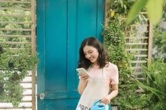Jardinier f?minin ? l'aide du t?l?phone portable tout en arrosant dans son jardin photographie stock