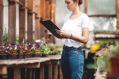 Jardinier f?minin travaillant dans le jardin avec des fleurs photo stock