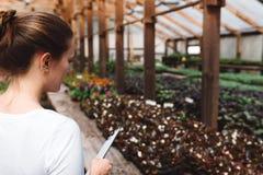 Jardinier f?minin travaillant dans le jardin avec des fleurs photo libre de droits