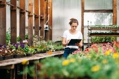 Jardinier f?minin travaillant dans le jardin avec des fleurs photographie stock
