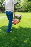 Jardinier masculin coupant l'herbe avec la tondeuse à gazon images libres de droits
