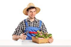 Jardinier masculin s'asseyant à une table avec des usines photo stock