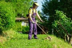 Jardinier professionnel à l'aide d'un coupe-rives dans le jardin images stock