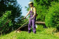 Jardinier professionnel à l'aide d'un coupe-rives dans le jardin photos libres de droits
