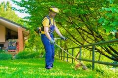 Jardinier professionnel à l'aide d'un coupe-rives dans le jardin photos stock