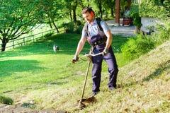 Jardinier professionnel à l'aide d'un coupe-rives dans le jardin photographie stock libre de droits