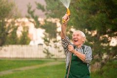 Jardinier supérieur avec le tuyau de l'eau Photographie stock libre de droits