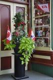 Jardiniere mit verschiedenen Blumen und kanadischen Flaggen in gesehenem Stadtzentrum von Niagara-auf-d-See von Ontario-Provinz Stockfoto