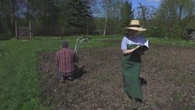 Jardiniers sur le champ près du cultivateur banque de vidéos