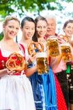 Jardín de la cerveza - amigos que beben en Pub de Baviera Imagen de archivo libre de regalías