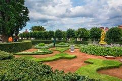 Jardín del palacio de Monplaisir El portero de sexo femenino barre la basura Foto de archivo libre de regalías