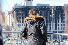 Jared Leto, die zich door een metaalomheining bevinden, kijkt neer op een brandwond het uitbouwen en een tentstad op Maidan Nezal stock afbeelding