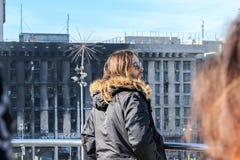 Jared Leto, die zich door een metaalomheining bevinden, kijkt neer op een brandwond het uitbouwen en een tentstad op Maidan Nezal stock foto