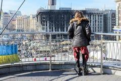 Jared Leto, die zich door een metaalomheining bevinden, kijkt neer op een brandwond het uitbouwen en een tentstad op Maidan Nezal royalty-vrije stock afbeelding