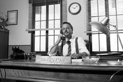 jaren '50bureau: directeur die aan de telefoon werken Stock Fotografie