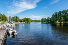 People on a moored motorboat at a boat refueling station. JARFALLA, SWEDEN - JUNE 9, 2018: Seascape front view of people on a moored motorboat at a boat royalty free stock photo