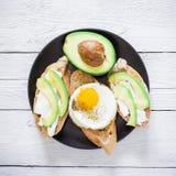 Jarosz kanapki z avocado i jajkiem na zmroku talerzu na drewnianym stole Mieszkanie nieatutowy Odgórny widok Smakowity karmowy po Obraz Stock