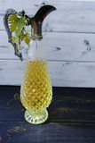 Jarra antigua del vino con las hojas del vino blanco y de la uva Imágenes de archivo libres de regalías