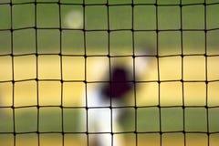 Jarra borrosa del béisbol vista a través de la red Fotografía de archivo