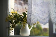 Jarra con las flores amarillas en la ventana Imágenes de archivo libres de regalías
