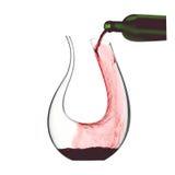Jarra cristalina elegante con el vino rojo que es vertido en él Fotos de archivo libres de regalías