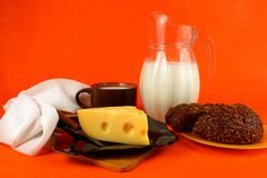 Jarra de leche, de queso y de pan en un fondo anaranjado Foto de archivo