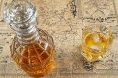 Jarra del whisky o del brandy con un vidrio de whisky en una tabla, cubierto en mapa viejo del papel de pergamino Foco suave imagenes de archivo