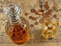 Jarra del whisky o del brandy, monedas británicas con un vidrio de whisky en una tabla Foco suave fotografía de archivo libre de regalías