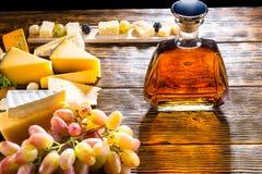Jarra del whisky o del brandy con queso y uvas Imágenes de archivo libres de regalías
