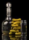 Jarra, vidrio con la vodka y pepinos conservados en vinagre aislados en fondo negro Fotos de archivo