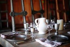 jarra y cubiertos del agua de la porcelana en la tabla de banquete Fotografía de archivo libre de regalías